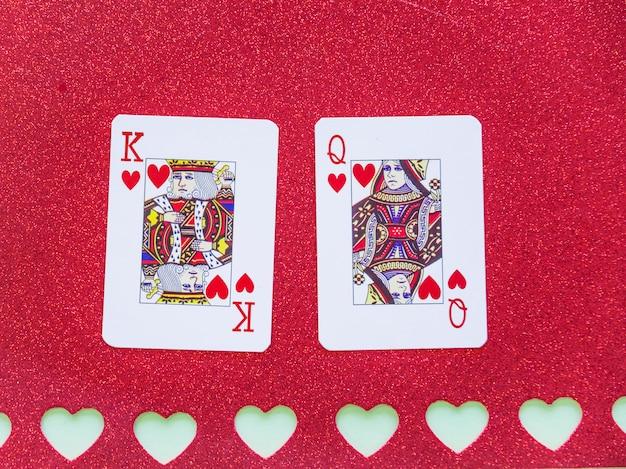 Rey y reina de corazones jugando a las cartas sobre papel