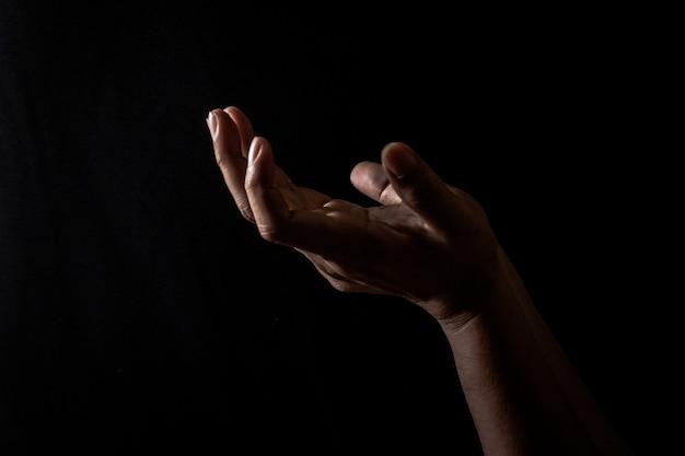 Rezando la mano a dios para cumplir la esperanza de uno sobre fondo negro, reza la mano ofreciendo respeto a dios