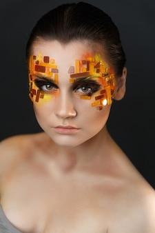 Rhinestones naranjas y rojos en una cara de la muchacha