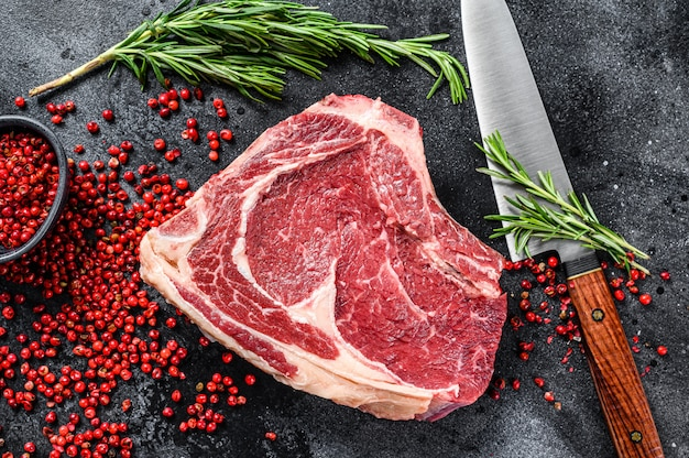 Ribeye en el hueso o filete de vaquero en carne de res de mármol crudo en mesa negra.