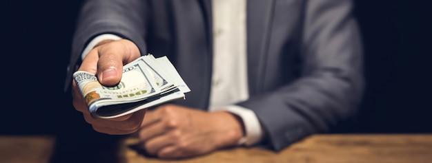 Rico empresario sosteniendo y dando dinero en dólares estadounidenses en cuarto oscuro privado