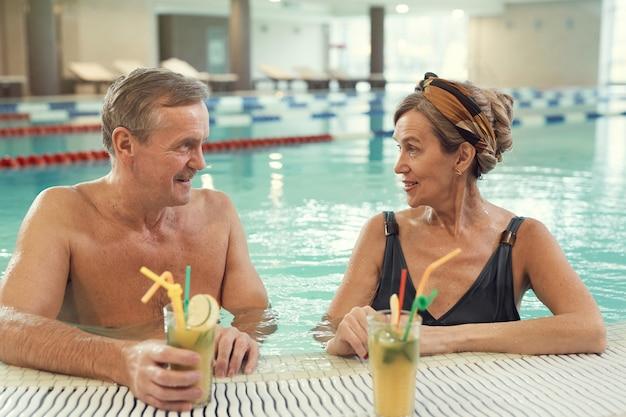Rico pareja de ancianos en la piscina