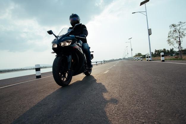 Rider moto en la carretera. divirtiéndose conduciendo el camino vacío
