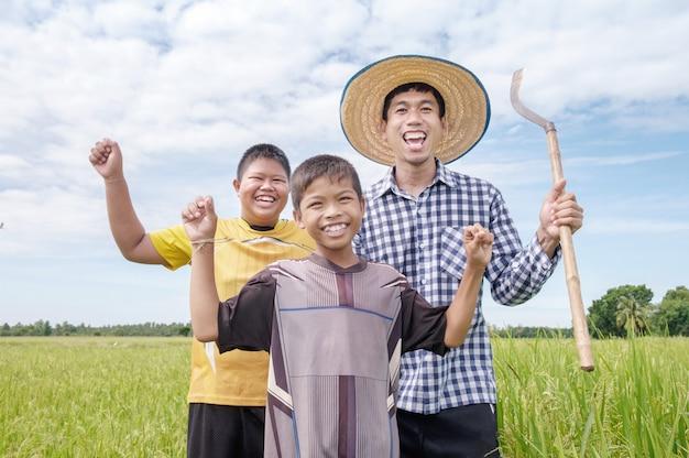 Ríe feliz hombre agricultor asiático y dos niños sonríen y sostienen herramientas en el campo de arroz verde