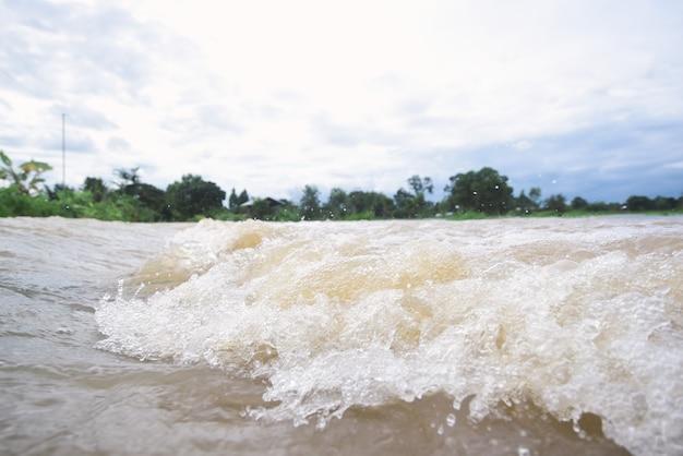 Riegue la inundación en el río después de fuertes lluvias en tailandia.