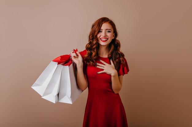 Riendo a adorable niña sosteniendo bolsas de papel de la tienda. magnífica dama caucásica posando después de ir de compras.