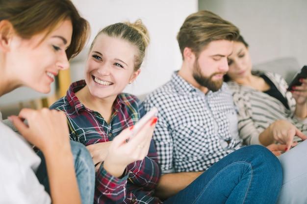 Riendo amigos con gadgets en el sofá