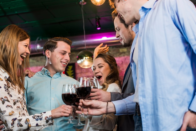 Riendo amigos hombres y mujeres en el bar disfrutando de bebidas