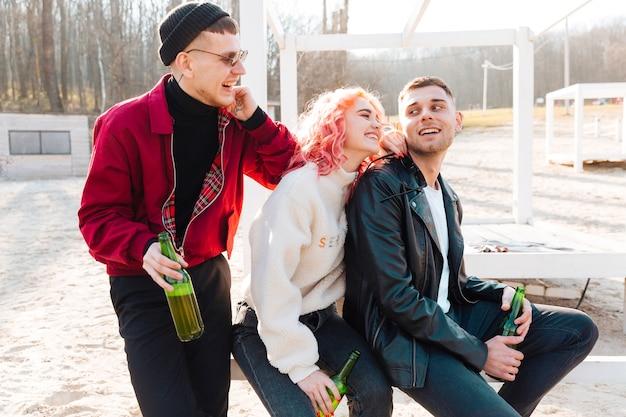 Riendo amigos inconformistas con cerveza divertirse juntos