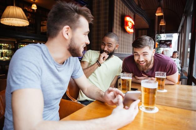 Riendo amigos varones mirando smartphone en pub de cerveza