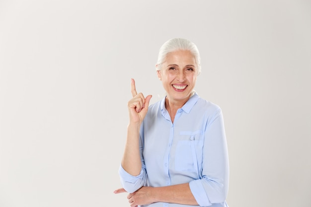 Riendo anciana canosa con camisa azul, apuntando con el dedo hacia arriba