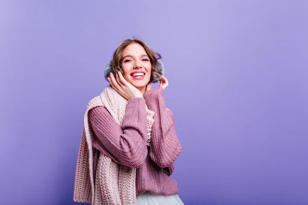 Riendo a la chica de moda en auriculares de invierno posando foto interior de mujer feliz inspirada en elegantes accesorios sonriendo en la pared púrpura.