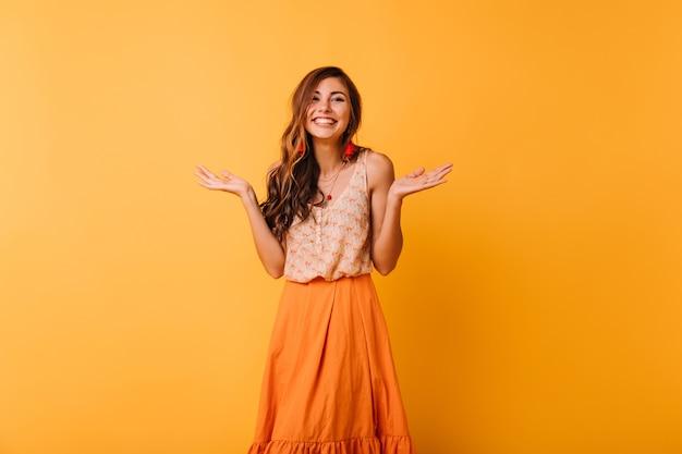 Riendo a chica optimista con pie de peinado largo en naranja. señora jocund con cabello ondulado disfrutando de la vida.
