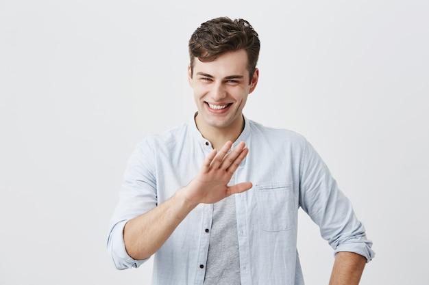 Riendo un chico apuesto positivo vestido con una camisa azul sobre una camiseta que muestra un gesto de parada, pidiendo que deje de bromear, ya que está cansado de reír. joven con elegante corte de pelo sonriendo