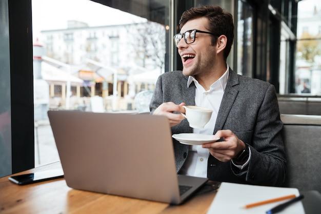 Riendo empresario en anteojos sentado junto a la mesa en la cafetería con computadora portátil y una taza de café mientras mira a la ventana