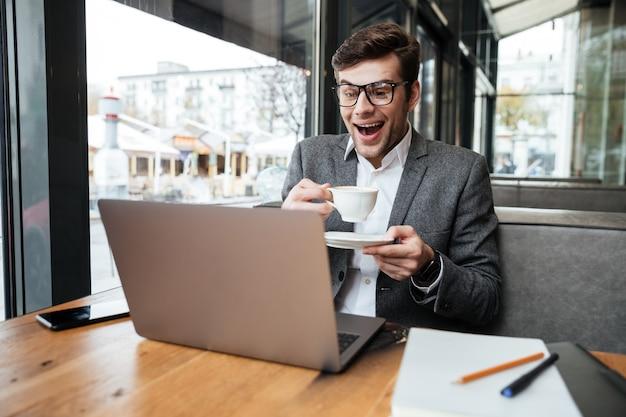 Riendo empresario en anteojos sentado junto a la mesa en la cafetería con una taza de café mientras mira a la computadora portátil