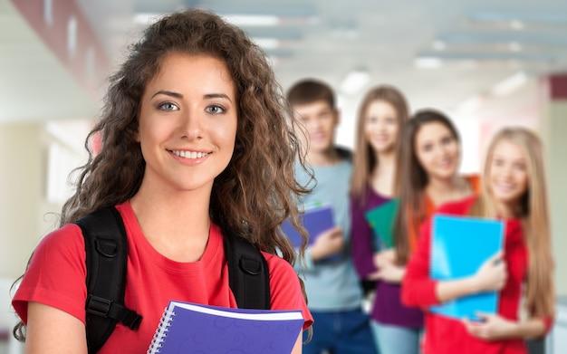 Riendo estudiante mexicana con un grupo de estudiantes en la biblioteca de la universidad - imagen