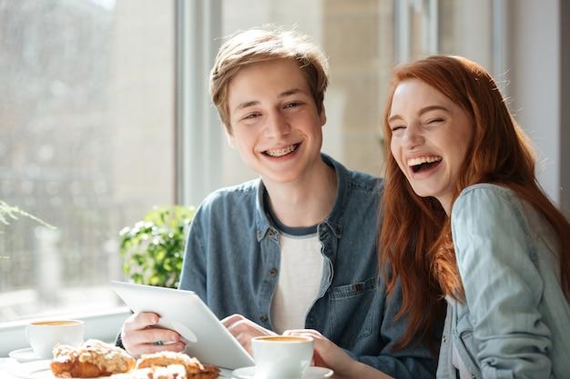 Riendo estudiantes sentados en la cafetería