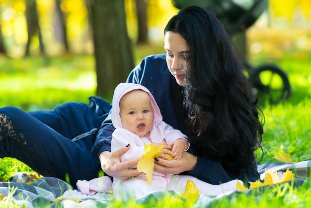Riendo feliz niña jugando con coloridas hojas amarillas de otoño mientras se abraza con su amorosa madre en una manta en el parque