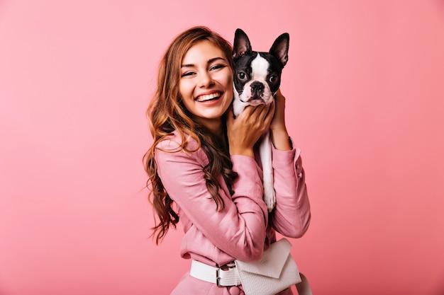 Riendo a hermosa mujer sosteniendo a su cachorro. retrato de linda chica jengibre posando en rosa con bulldog francés.