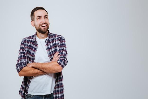 Riendo hombre barbudo en camisa con brazos cruzados