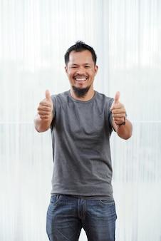 Riendo hombre filipino de pie delante de la ventana iluminada con los pulgares hacia arriba