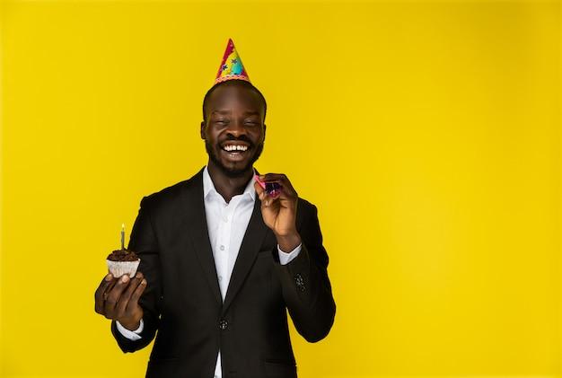 Riendo a joven afroamericano en traje negro y sombrero de cumpleaños con velas encendidas