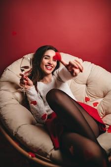 Riendo a mujer adorable con copa de vino divirtiéndose