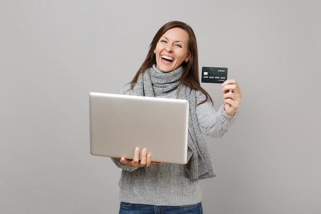 Riendo a mujer joven en suéter gris, bufanda trabajando en computadora portátil con tarjeta bancaria de crédito aislada sobre fondo de pared gris. consulta de tratamiento en línea de estilo de vida saludable, concepto de estación fría.