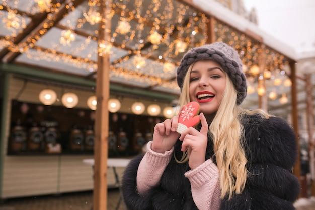Riendo mujer rubia sosteniendo una deliciosa galleta de jengibre contra la decoración ligera en la feria de navidad en kiev