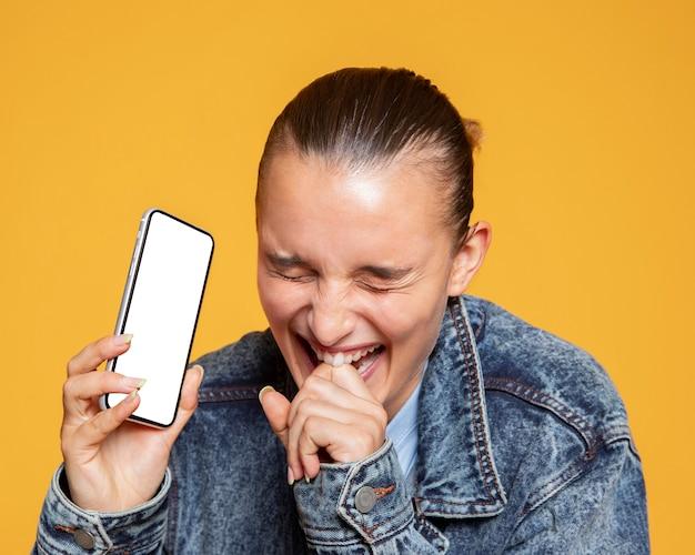 Riendo mujer sosteniendo smartphone