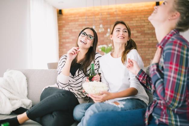 Riendo a mujeres jóvenes con bocadillos en el sofá