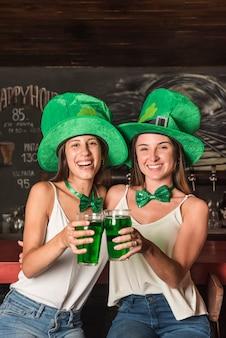 Riendo a mujeres jóvenes con sombreros de san patricio abrazando y sosteniendo vasos de bebida en la barra del bar