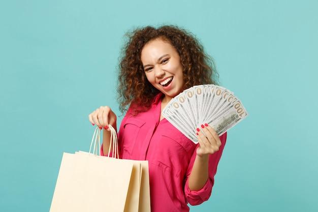 Riendo niña africana mantenga la bolsa del paquete con compras después de ir de compras, fanático del dinero en billetes de dólar, dinero en efectivo aislado sobre fondo azul turquesa. concepto de estilo de vida de personas. simulacros de espacio de copia.