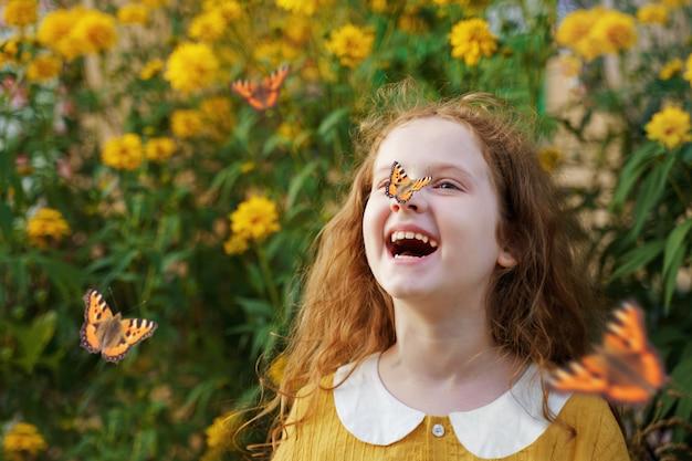 Riendo niña rizada con una mariposa en la nariz.