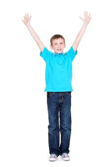 Riendo a niño feliz con las manos levantadas en una camiseta azul, aislada sobre fondo blanco.