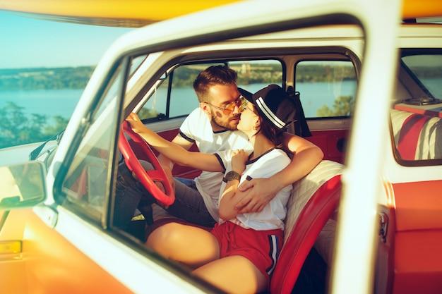Riendo pareja romántica sentada en el coche mientras está en un viaje por carretera en verano