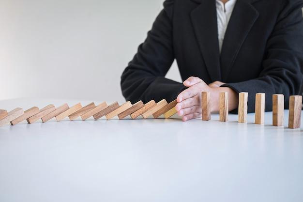 Riesgo y estrategia en los negocios, imagen de la mano que detiene el colapso de caída efecto de dominó del bloque de madera desde el bloqueo continuo derrumbado, prevención y desarrollo hasta la estabilidad