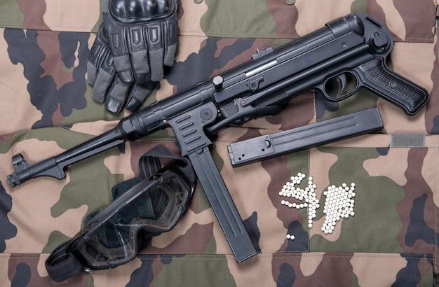 Rifle airsoft con gafas protectoras, guantes y balas blancas.