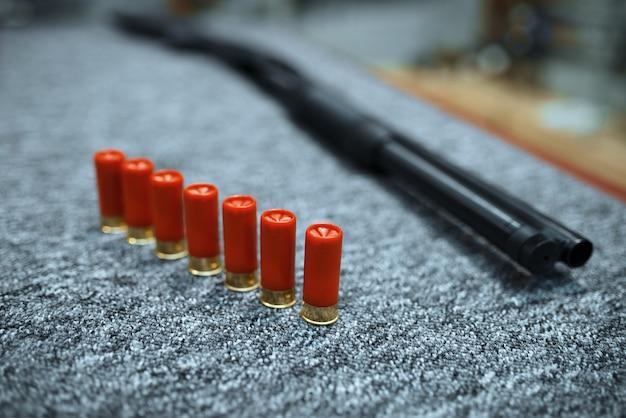 Rifle y fila de munición en la armería, primer plano, nadie. equipo para cazadores en stand en almacén de armas, pasatiempo de caza y tiro deportivo