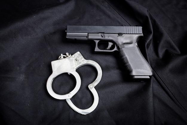 Rifle, pistola, cuchillo con funda, brújula y cuaderno con bolígrafo sobre tela negra