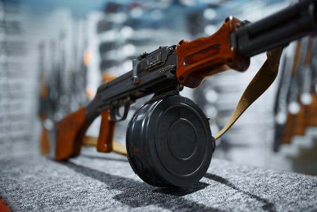 Rifle con un primer plano de la revista de tambor, escaparate en la armería. equipo para cazadores en stand en almacén de armas