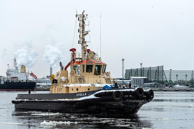 Riga, letonia - 9 de febrero de 2021: el remolcador regresa al puerto de carga en una fría y brumosa mañana de invierno