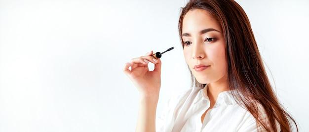 El rimel compone a la mujer joven asiática de la belleza con el pelo largo oscuro en el fondo blanco