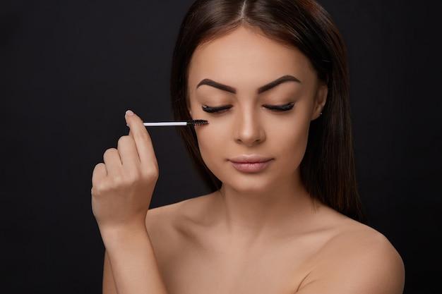 Rimel, maquillaje de belleza, piel suave y fresca y pestañas largas y gruesas y gruesas aplicando rimel con cepillo cosmético, extensiones de pestañas, pestañas postizas,