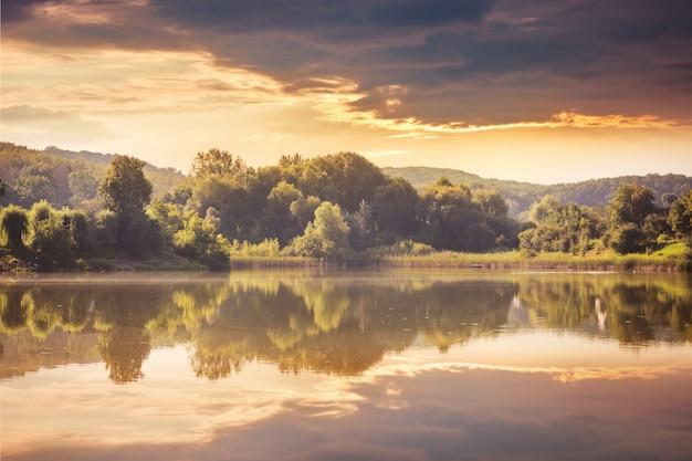 Río y bosque al atardecer. exhibe árboles y nubes en el agua del lago.