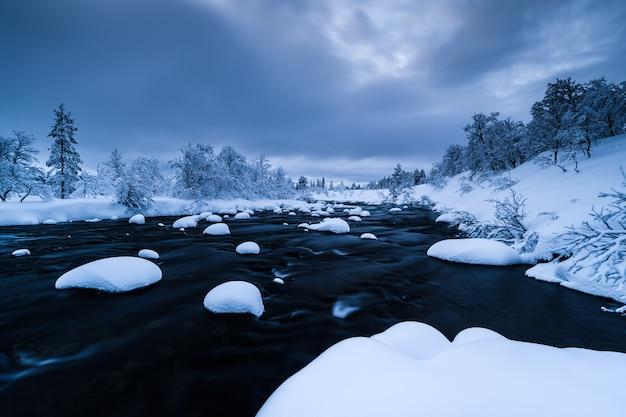 Río con nieve y un bosque cerca cubierto de nieve en invierno en suecia