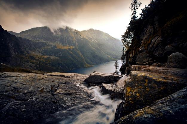 Río en el paisaje de niebla de las montañas.