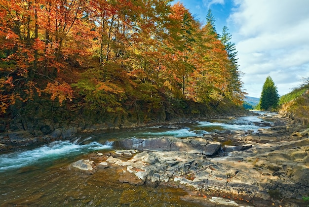 Río rocky autumn mountain con pequeñas cascadas