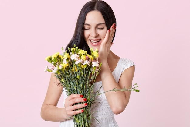 Risa atractiva joven modelo morena con los ojos cerrados sosteniendo hermosas flores en una mano, tocando su rostro con la otra